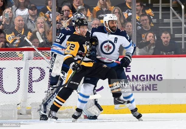 Patric Hornqvist of the Pittsburgh Penguins and Dustin Byfuglien of the Winnipeg Jets battle in front of the net at PPG Paints Arena on October 26...