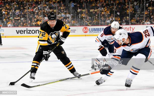 Patric Hornqvist of the Pittsburgh Penguins handles the puck front of Leon Draisaitl of the Edmonton Oilers at PPG Paints Arena on October 24 2017 in...