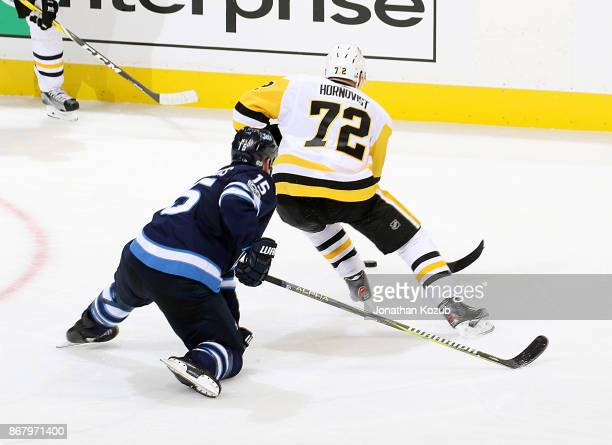 Patric Hornqvist of the Pittsburgh Penguins plays the puck away from Matt Hendricks of the Winnipeg Jets during second period action at the Bell MTS...