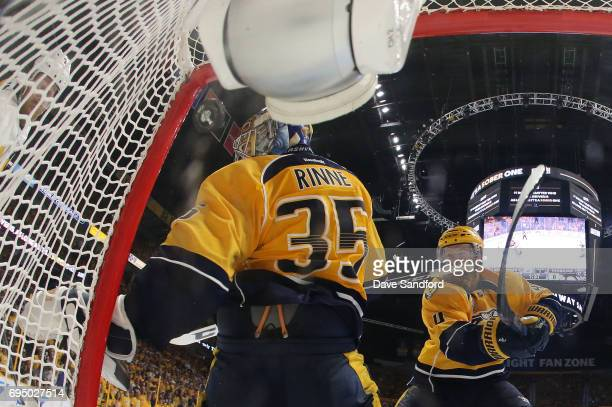 Patric Hornqvist of the Pittsburgh Penguins shoots the puck off goaltender Pekka Rinne of the Nashville Predators which goes into the net for a goal...