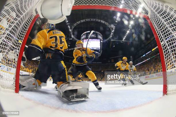 Patric Hornqvist of the Pittsburgh Penguins shoots the puck off goaltender Pekka Rinne of the Nashville Predators on the short side which goes into...