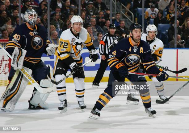 Patric Hornqvist of the Pittsburgh Penguins skates between Robin Lehner and Josh Gorges of the Buffalo Sabres during an NHL game at the KeyBank...