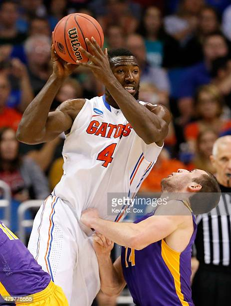 Patric Young of the Florida Gators charges into Sam Rowley of the Albany Great Danes in the second half during the second round of the 2014 NCAA...