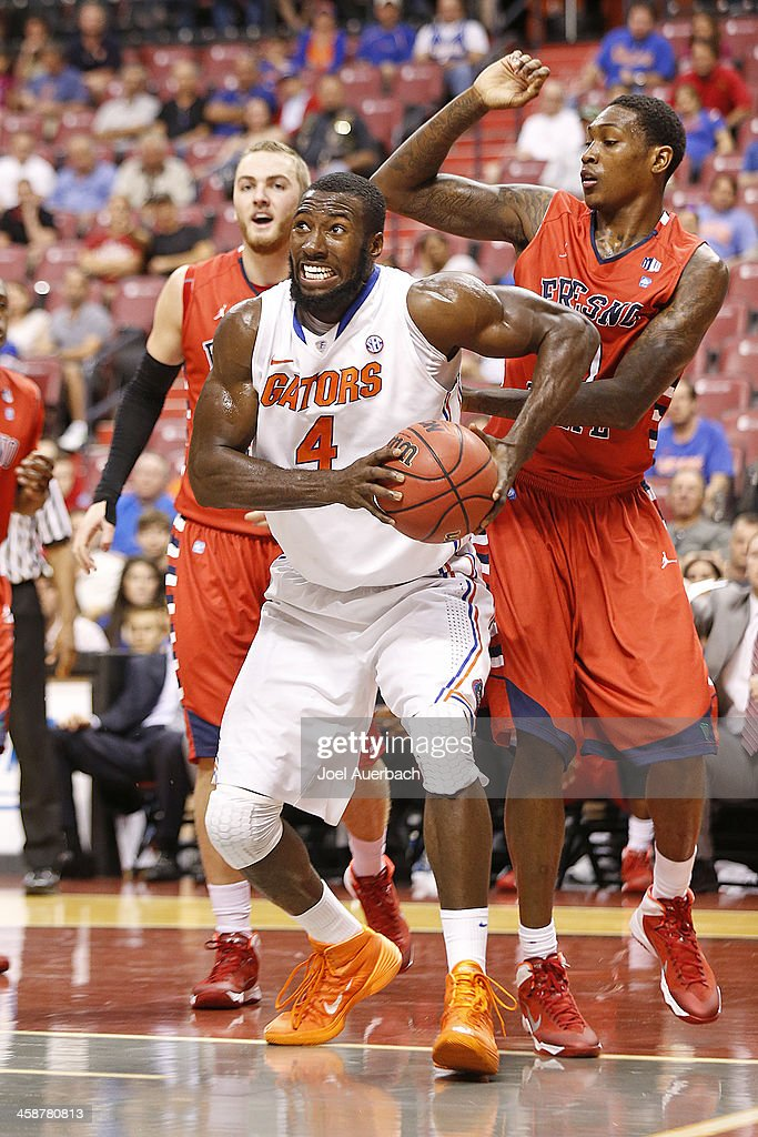 Patric Young #4 of the Florida Gators dribbles to the basket past Alex Davis #10 of the Fresno State Bulldogs during the MetroPCS Orange Bowl Basketball Classic on December 21, 2013 at the BB&T Center in Sunrise, Florida. Florida defeated Fresno State 66-49.