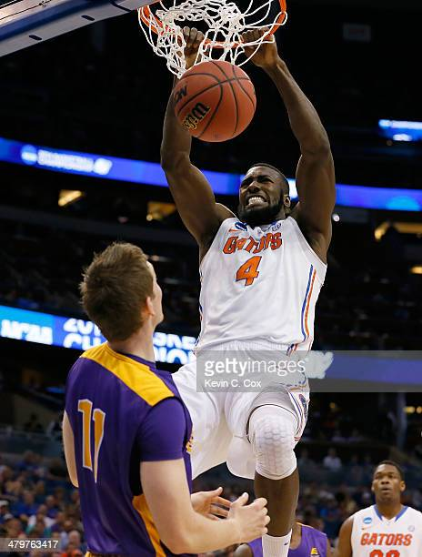 Patric Young of the Florida Gators dunks over Luke Devlin of the Albany Great Danes in the first half during the second round of the 2014 NCAA Men's...