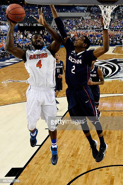 Patric Young of the Florida Gators goes to the basket as DeAndre Daniels of the Connecticut Huskies defends during the NCAA Men's Final Four...