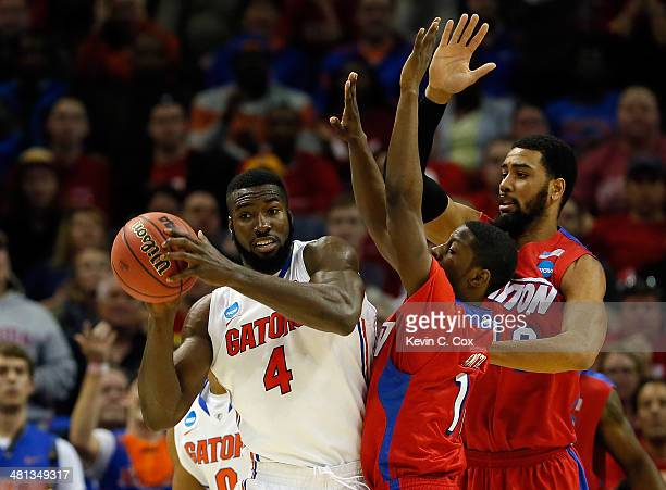 Patric Young of the Florida Gators looks to pass as d1132 and Devon Scott of the Dayton Flyers defend during the south regional final of the 2014...