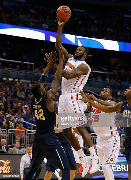 Patric Young of the Florida Gators shoots over Talib Zanna of the Pittsburgh Panthers in the second half during the third round of the 2014 NCAA...