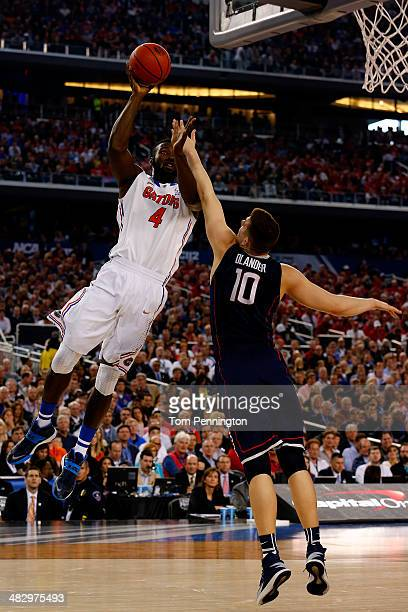 Patric Young of the Florida Gators takes a shot as Tyler Olander of the Connecticut Huskies defends during the NCAA Men's Final Four Semifinal at ATT...