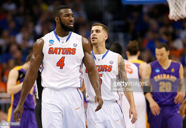 Patric Young reacts with teammate Scottie Wilbekin of the Florida Gators in the second half against the Albany Great Danes during the second round of...