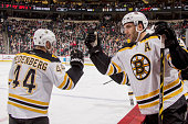 Patrice Bergeron and Dennis Seidenberg of the Boston Bruins celebrate after scoring a goal against the Minnesota Wild during the game on December 17...