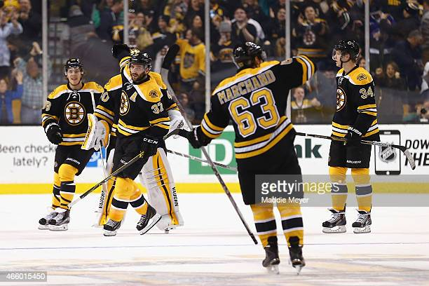 Patrice Bergeron David Pastrnak and Carl Soderberg congratulate Brad Marchand of the Boston Bruins after he scored the game winning goal during a...