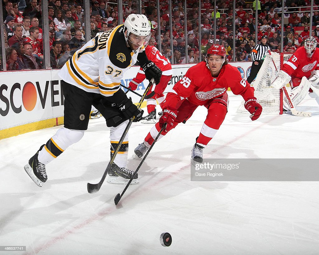 Patrice Bergeron #37 of the Boston Bruins and Danny DeKeyser #65 of the Detroit Red Wings battle for the puck during Game Four of the First Round of the 2014 Stanley Cup Playoffs on April 24, 2014 at Joe Louis Arena in Detroit, Michigan.