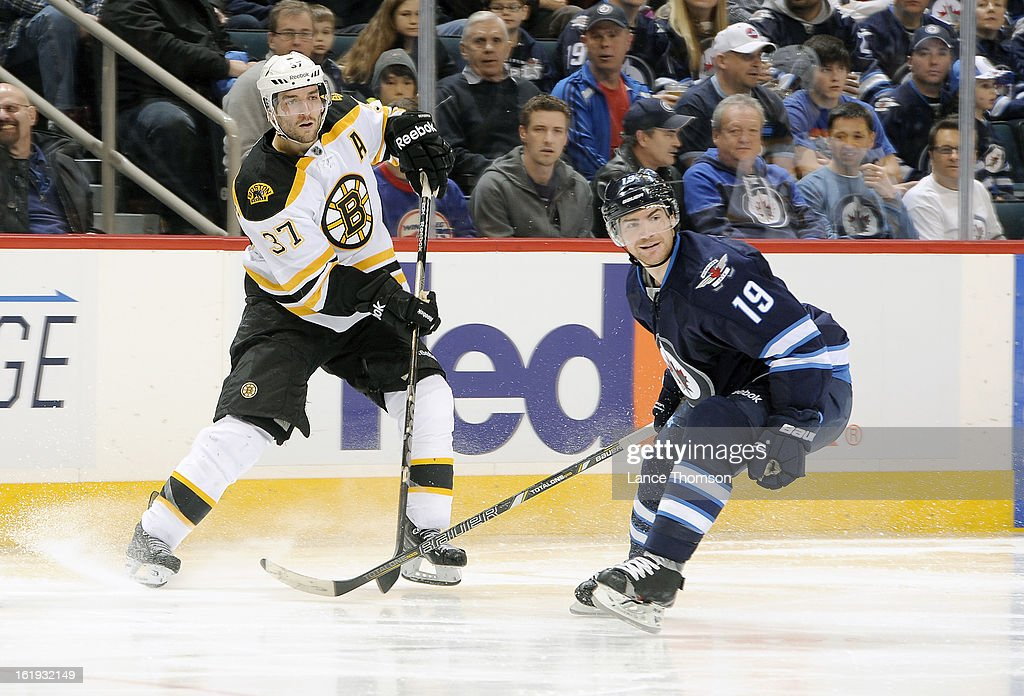 Patrice Bergeron #37 of the Boston Bruins and Jim Slater #19 of the Winnipeg Jets keep an eye on the play during third period action at the MTS Centre on February 17, 2013 in Winnipeg, Manitoba, Canada.