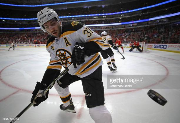 Patrice Bergeron of the Boston Bruins bounces the puck off of the glass against the Chicago Blackhawks at the United Center on April 2 2017 in...