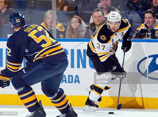 Patrice Bergeron of the Boston Bruins carries the puck along the boards against Alexander Sulzer of the Buffalo Sabres at First Niagara Center on...