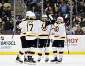 Patrice Bergeron of the Boston Bruins celebrates his game winning goal with teammates in overtime during the game against the Pittsburgh Penguins at...
