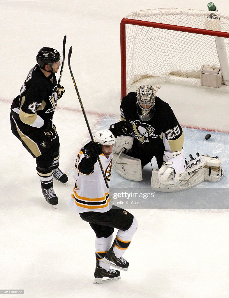 Patrice Bergeron #37 of the Boston Bruins celebrates his game-winning goal in overtime against Simon Despres #47 and Marc-Andre Fleury #29 of the Pittsburgh Penguins at Consol Energy Center on January 7, 2015 in Pittsburgh, Pennsylvania.