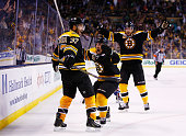 Patrice Bergeron of the Boston Bruins celebrates his tying goal in the third period with teammates Brad Marchand and Dougie Hamilton against the...