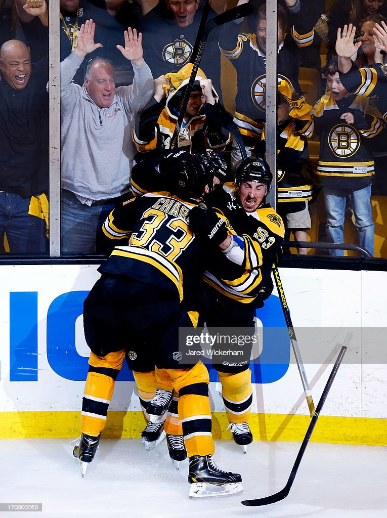 Patrice Bergeron of the Boston Bruins celebrates with Brad Marchand and Zdeno Chara after scoring the game winning goal in overtime to beat the...