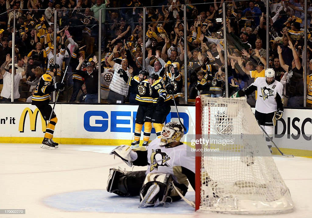 Patrice Bergeron of the Boston Bruins celebrates with Brad Marchand and Zdeno Chara after scoring the game winning goal in double overtime to beat...