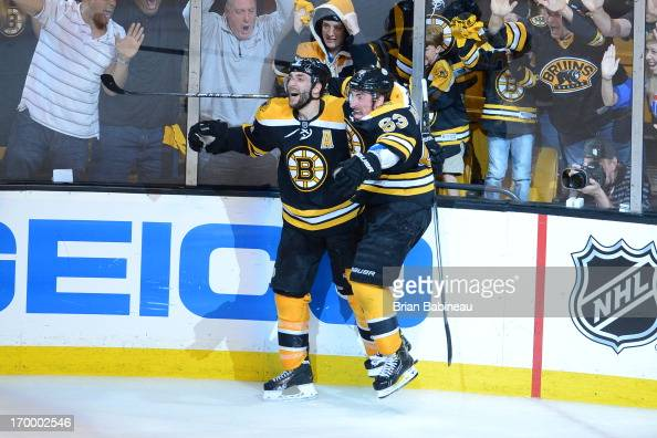 Patrice Bergeron of the Boston Bruins celebrates with Brad Marchand after scoring in overtime against the Pittsburgh Penguins in Game Three of the...