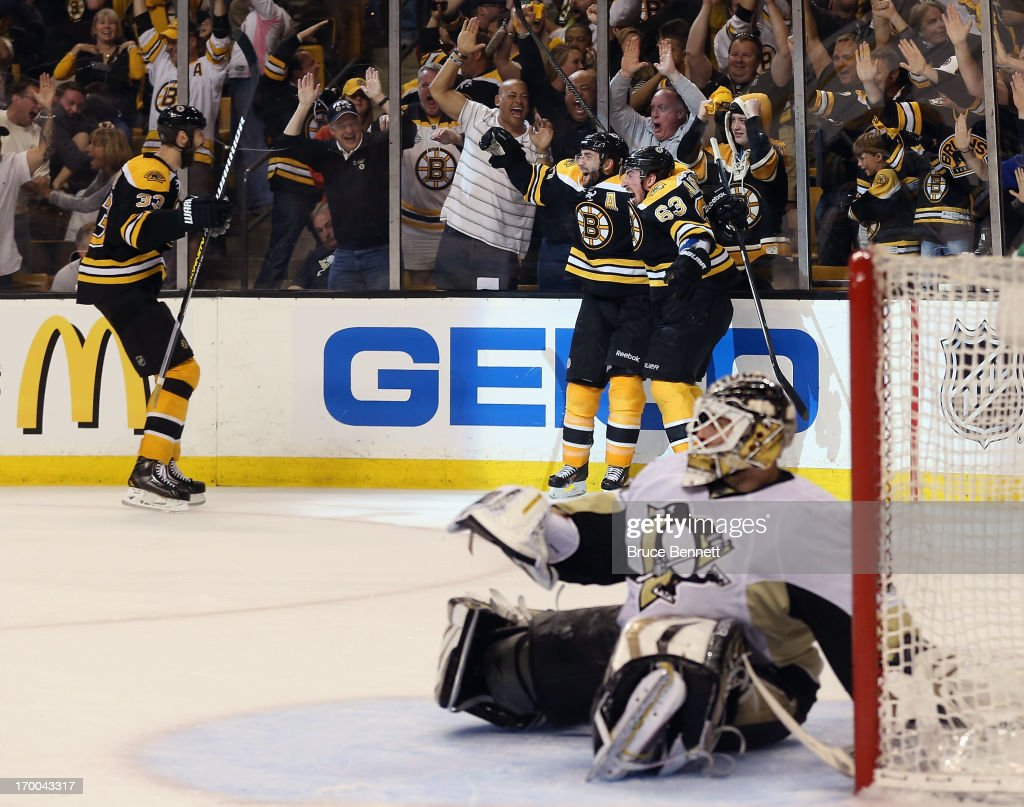 Patrice Bergeron of the Boston Bruins celebrates with Brad Marchand and Zdeno Chara after scoring the game winning goal against Tomas Vokoun of the...