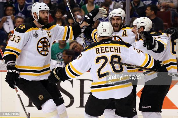 Patrice Bergeron of the Boston Bruins celebrates with his teammates Zdeno Chara Mark Recchi and Brad Marchand after scoring a goal in the first...
