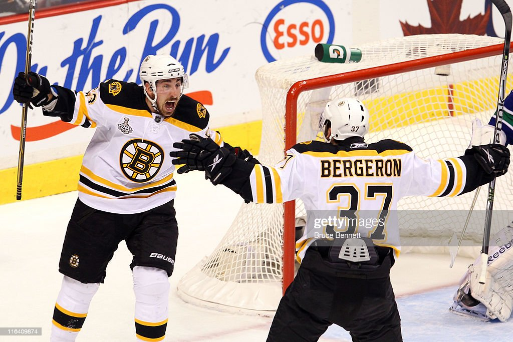 <a gi-track='captionPersonalityLinkClicked' href=/galleries/search?phrase=Patrice+Bergeron&family=editorial&specificpeople=204162 ng-click='$event.stopPropagation()'>Patrice Bergeron</a> #37 of the Boston Bruins celebrates with his teammates <a gi-track='captionPersonalityLinkClicked' href=/galleries/search?phrase=Brad+Marchand&family=editorial&specificpeople=2282544 ng-click='$event.stopPropagation()'>Brad Marchand</a> #63 after scoring a goal in the first period against Roberto Luongo #1 of the Vancouver Canucks during Game Seven of the 2011 NHL Stanley Cup Final at Rogers Arena on June 15, 2011 in Vancouver, British Columbia, Canada.