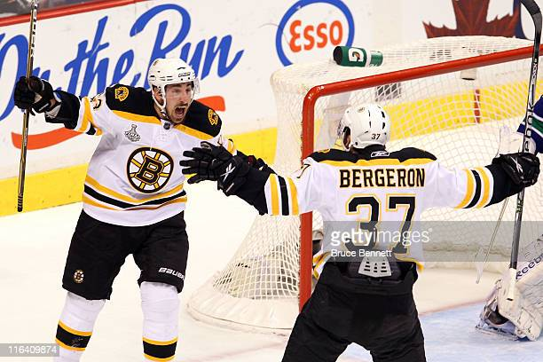 Patrice Bergeron of the Boston Bruins celebrates with his teammates Brad Marchand after scoring a goal in the first period against Roberto Luongo of...