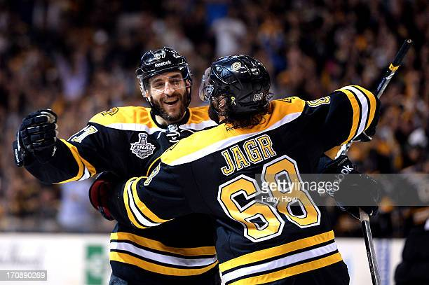 Patrice Bergeron of the Boston Bruins celebrates with Jaromir Jagr after a goal in the third period against the Chicago Blackhawks in Game Four of...