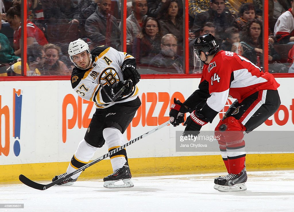 <a gi-track='captionPersonalityLinkClicked' href=/galleries/search?phrase=Patrice+Bergeron&family=editorial&specificpeople=204162 ng-click='$event.stopPropagation()'>Patrice Bergeron</a> #37 of the Boston Bruins chips the puck past <a gi-track='captionPersonalityLinkClicked' href=/galleries/search?phrase=Colin+Greening&family=editorial&specificpeople=7183741 ng-click='$event.stopPropagation()'>Colin Greening</a> #14 of the Ottawa Senators during an NHL game at Canadian Tire Centre on December 28, 2013 in Ottawa, Ontario, Canada.