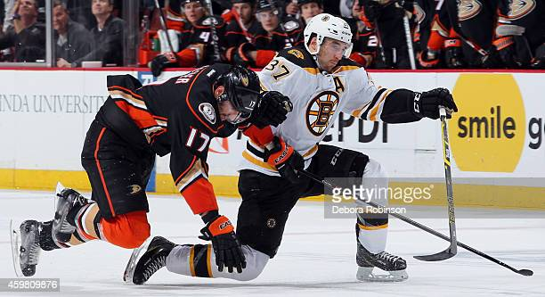 Patrice Bergeron of the Boston Bruins collides with Ryan Kesler of the Anaheim Ducks on December 1 2014 at Honda Center in Anaheim California