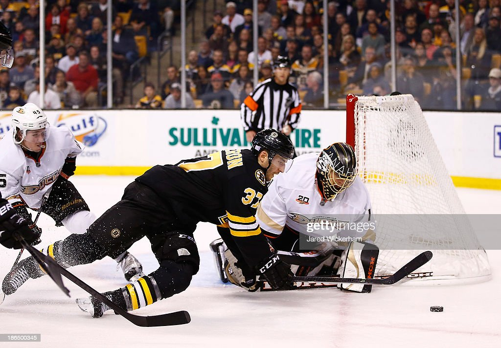 Patrice Bergeron #37 of the Boston Bruins dives for the puck in front of Jonas Hiller #1 of the Anaheim Ducks in overtime at TD Garden on October 31, 2013 in Boston, Massachusetts.