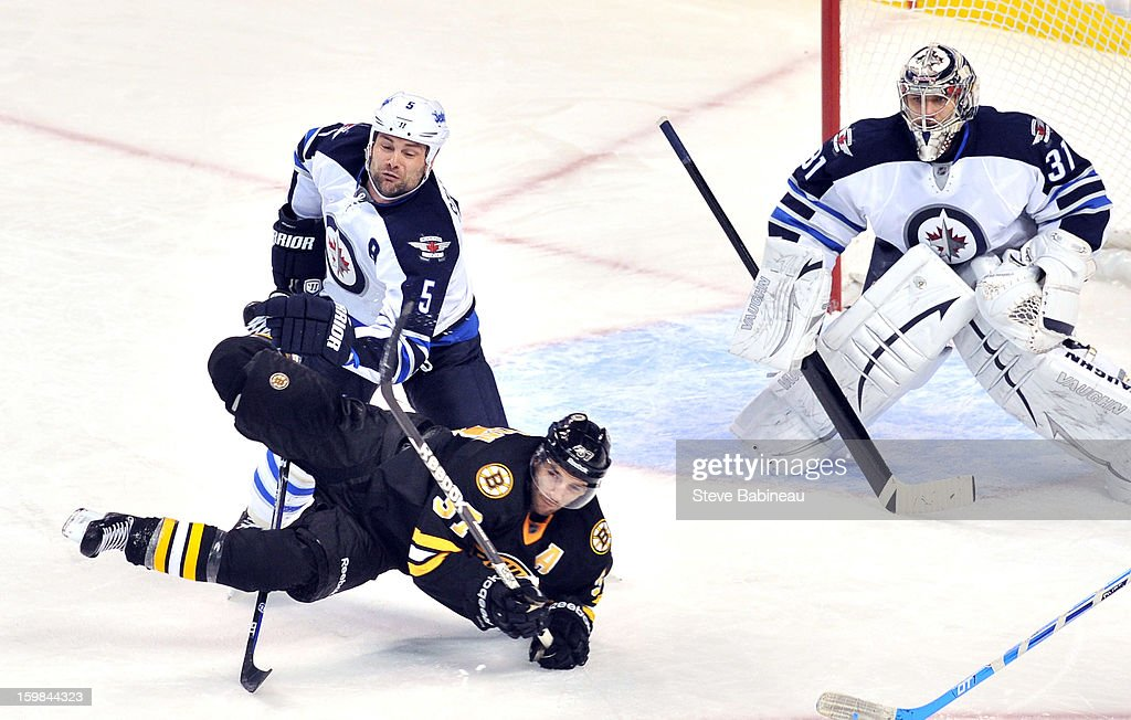 <a gi-track='captionPersonalityLinkClicked' href=/galleries/search?phrase=Patrice+Bergeron&family=editorial&specificpeople=204162 ng-click='$event.stopPropagation()'>Patrice Bergeron</a> #37 of the Boston Bruins dives in front of the net against Mark Stuart #5 and Ondrej Pavelec #31 of the Winnipeg Jets at the TD Garden on January 21, 2013 in Boston, Massachusetts.