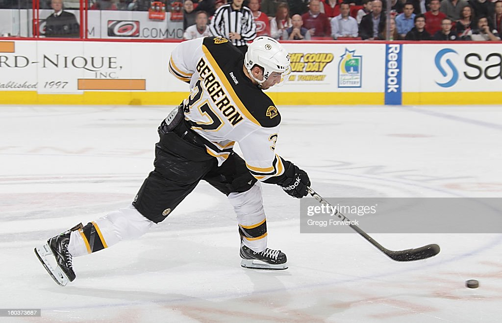 Patrice Bergeron #37 of the Boston Bruins fires a slap shot at the end of the period during an NHL game against the Carolina Hurricanes at PNC Arena on January 28, 2013 in Raleigh, North Carolina.