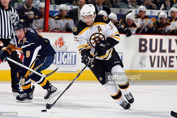 Patrice Bergeron of the Boston Bruins handles the puck against Derek Roy of the Buffalo Sabres on October 21 2008 at HSBC Arena in Buffalo New York