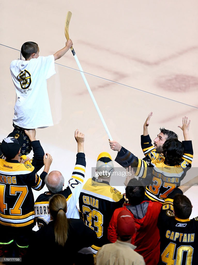 Patrice Bergeron #37 of the Boston Bruins hands a stick over the glass to a fan after defeating the Chicago Blackhawks 2-0 in Game Three of the 2013 NHL Stanley Cup Final at TD Garden on June 17, 2013 in Boston, Massachusetts.