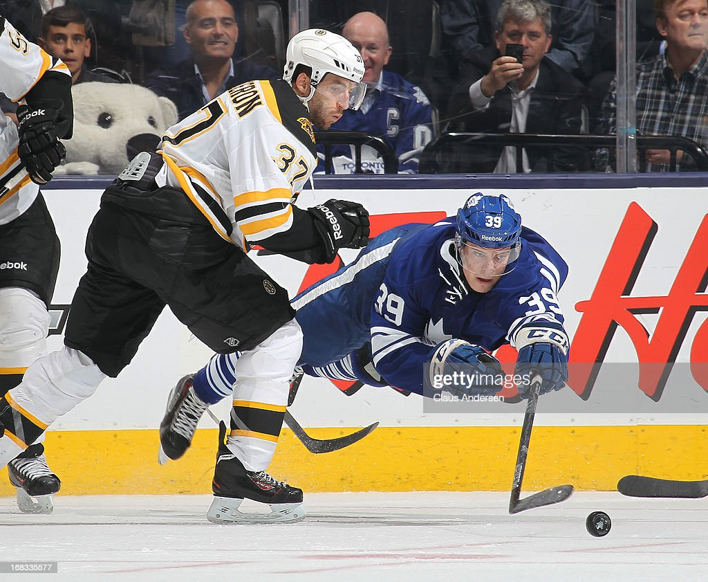 <a gi-track='captionPersonalityLinkClicked' href=/galleries/search?phrase=Patrice+Bergeron&family=editorial&specificpeople=204162 ng-click='$event.stopPropagation()'>Patrice Bergeron</a> #37 of the Boston Bruins knocks <a gi-track='captionPersonalityLinkClicked' href=/galleries/search?phrase=Matt+Frattin&family=editorial&specificpeople=5648435 ng-click='$event.stopPropagation()'>Matt Frattin</a> #39 of the Toronto Maple Leafs to the ice in Game Four of the Eastern Conference Quarterfinals during the 2013 NHL Stanley Cup Playoffs on May 8, 2013 at the Air Canada Centre in Toronto, Ontario, Canada. The Bruins defeated the Leafs 4-3 in overtime to take a 3-1 series lead.