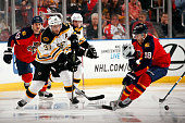 Patrice Bergeron of the Boston Bruins passes the puck by Reilly Smith of the Florida Panthers at the BBT Center on October 30 2015 in Sunrise Florida