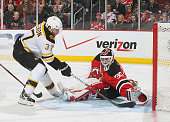 Patrice Bergeron of the Boston Bruins puts the puck past Martin Brodeur of the New Jersey Devils for a secondperiod goal during the game at the...