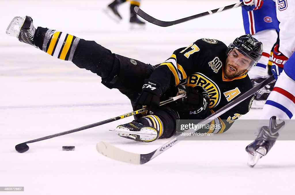 Patrice Bergeron #37 of the Boston Bruins reaches for a loose puck while laying on the ice in the third period against the Montreal Canadiens during the game at TD Garden on March 24, 2014 in Boston, Massachusetts.