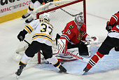 Patrice Bergeron of the Boston Bruins scores a goal against Corey Crawford of the Chicago Blackhawks in the first period at the United Center on...