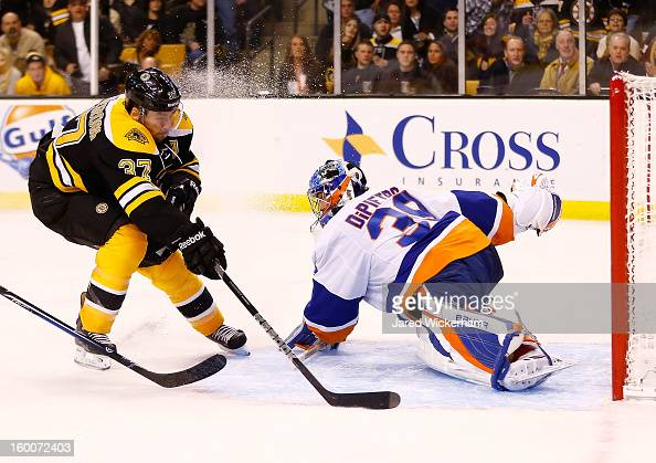 Patrice Bergeron of the Boston Bruins scores a goal around Rick DiPietro of the New York Islanders during the game on January 25 2013 at TD Garden in...