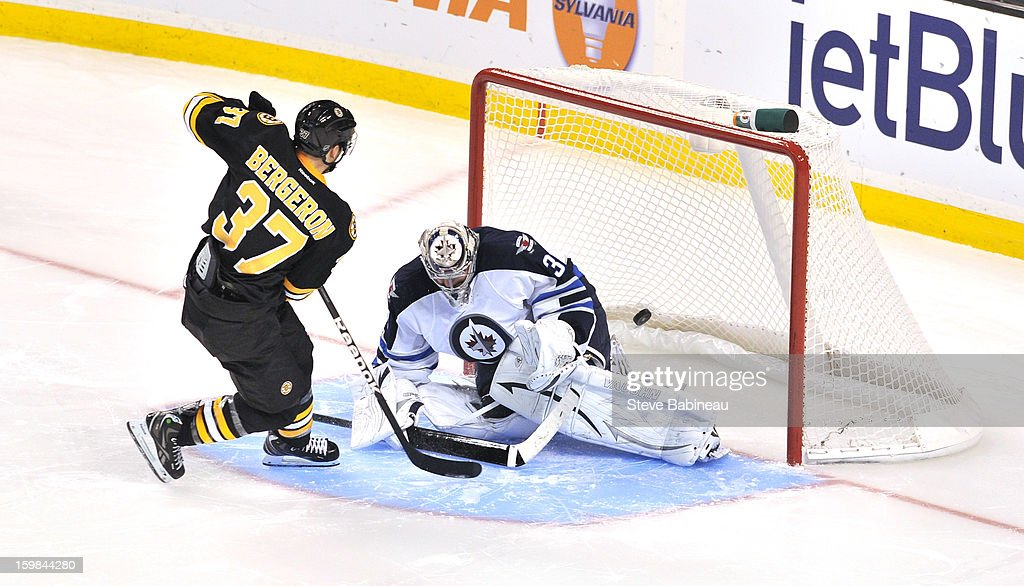 <a gi-track='captionPersonalityLinkClicked' href=/galleries/search?phrase=Patrice+Bergeron&family=editorial&specificpeople=204162 ng-click='$event.stopPropagation()'>Patrice Bergeron</a> #37 of the Boston Bruins scores in a shoot out against Ondrej Pavelec #31 of the Winnipeg Jets at the TD Garden on January 21, 2013 in Boston, Massachusetts.