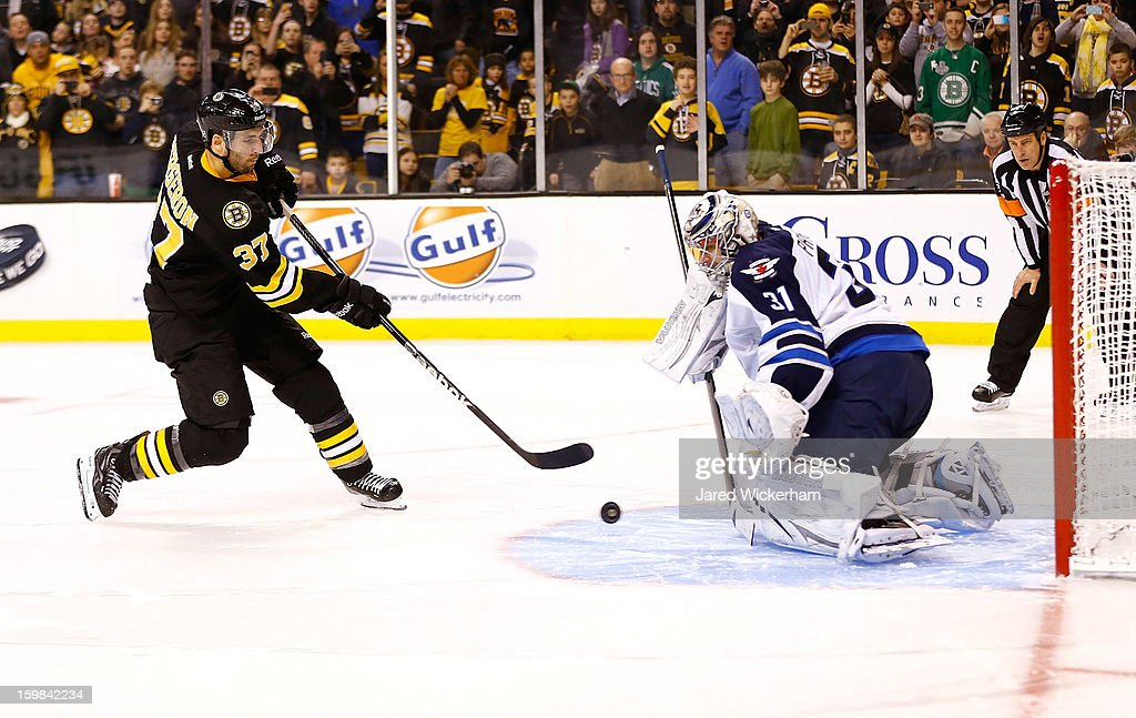 Patrice Bergeron #37 of the Boston Bruins shoots the second shootout goal on Ondrej Pavelec #31 of the Winnipeg Jets before scoring during the game on January 21, 2013 at TD Garden in Boston, Massachusetts.