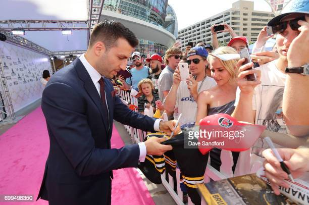 Patrice Bergeron of the Boston Bruins signs an autograph as he arrives on the magenta carpet for the 2017 NHL Awards at TMobile Arena on June 21 2017...
