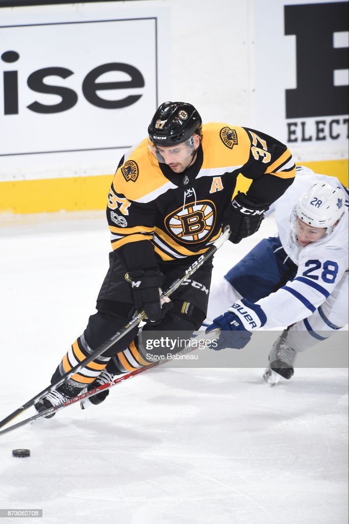 Patrice Bergeron #37 of the Boston Bruins skates with the puck against Connor Brown #28 of the Toronto Maple Leafs at the TD Garden on November 11, 2017 in Boston, Massachusetts.