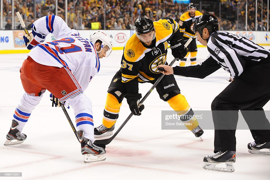 Patrice Bergeron #37 of the Boston Bruins takes a face off against Derek Stepan #21 of the New York Rangers in Game Two of the Eastern Conference Semifinals during the 2013 NHL Stanley Cup Playoffs at TD Garden on May 19, 2013 in Boston, Massachusetts.