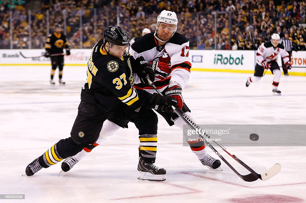 Patrice Bergeron #37 of the Boston Bruins takes a shot against Ilya Kovalchuk #17 of the New Jersey Devils during the game on January 29, 2013 at TD Garden in Boston, Massachusetts.